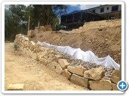 Boulder retaining wall before completion